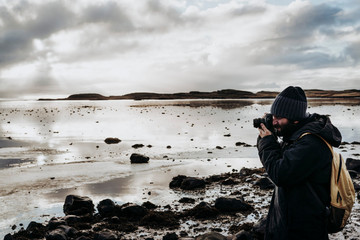 Anonymous tourist with camera against lake in Iceland