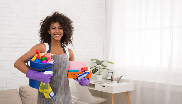 Smiling black woman posing with cleaning supplies