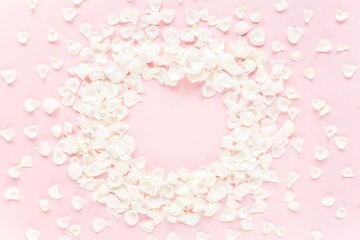 Frame made of beige petals roses on pink background. Flat lay, top view. Valentine's background. Valentine's Day concept.