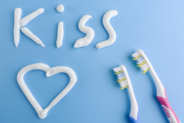 A heart and a text made with white toothpaste on blue. The word KISS and a heart on blue. Toothpaste shapes and toothbrushes on blue.