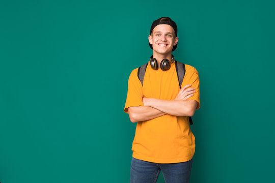 Happy teenager with crossed arms over turquoise background