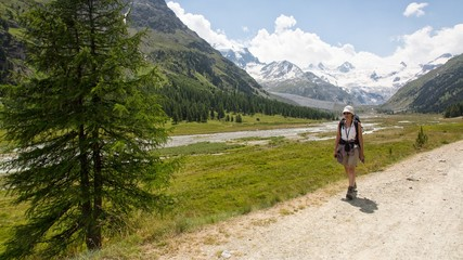 Hiker in Roseg valley, in the background the glacier and the Piz Roseg in the Bernina mountain group, Pontresina, Engadine, Canton of Grisons, Switzerland, Europe