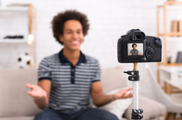 Happy video blogger on screen of modern camera