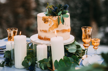 Amazing beige cake decorated with flowers, standing on the table near to candles