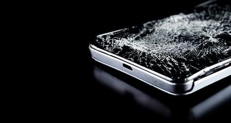 Broken smartphone on black background. Repair of computer equipment. Broken phone