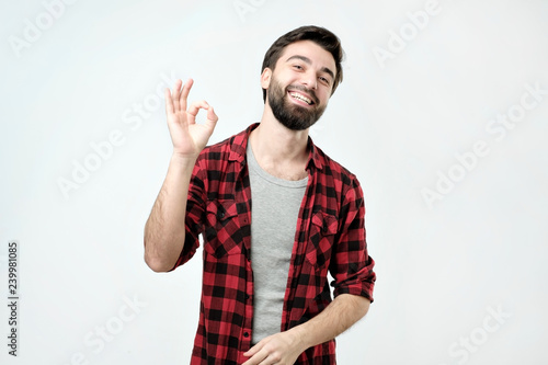31688cd5 Everything is OK concept. Happy young man in shirt gesturing OK sign and  smiling.