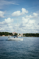 Sail boat and clear blue water in a Croatian bay, golden cape