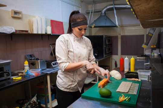 woman prepares delicious fresh sushi in the kitchen at restaurant