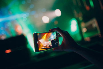 Mobile phone in hand. Photo and video on your phone at a concert or party.