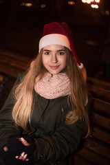 The portrait of a young blonde girl outside in the evening dressing winter clothes and a Christmas Santa holiday hat