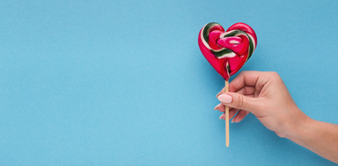 Love conceptual background, hand with heart shaped lollipop