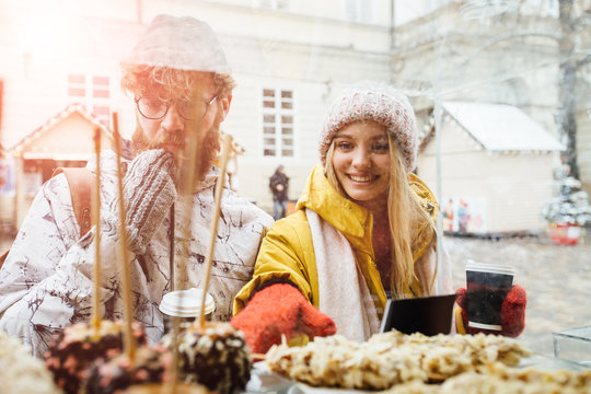 Excited hipster couple choosing cake while spending time together in outdoors winter christmas fair. Surprised happy blond woman and beard caucasian man point in show case by hand in red mitten.