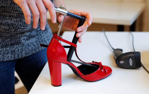 A fitting model measures the sizes of a shoe which goes on sale at the online shop of fashion retailer Zalando in Berlin