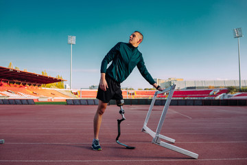 Athlete with prosthetic leg on running track