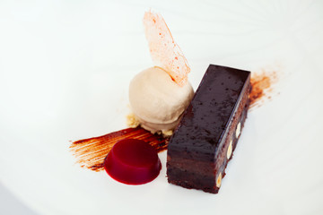 Chocolate brownie, served with ice cream on a white plate