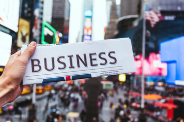 partial view of man holding business newspaper with blurry new york city street view on background