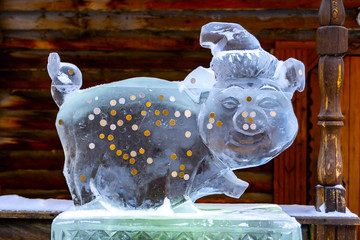 Ice sculpture-a Pig - a symbol of 2019. Ice pig happiness with coins