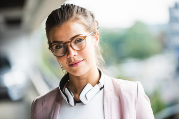 Portrait of a young businesswoman with headphones around her neck