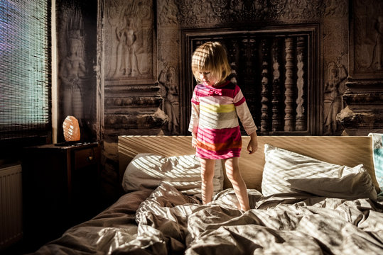 Girl standing on bed at home