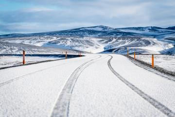 Reifenspuren im Schnee auf Strasse in Island