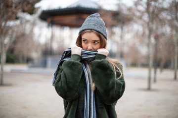 Pretty young female in warm clothes wrapping in scarf and looking away while standing on blurred background of autumn park on really cold day