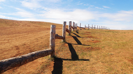 Beautiful summer landscape of pasture for cattle. Wooden fence in prairie, blue sky with clouds. Separation barrier of agricultural land in steppe.
