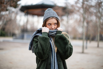 Young woman wrapping in scarf in autumn park