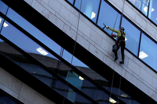 A man cleans the windows of the Baillie Gifford offices in Edinburgh