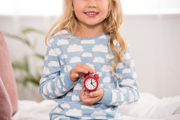 partial view of adorable kid sitting on bed with small clock in hands