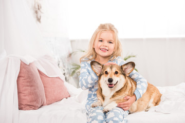 smiling child in pajamas embracing and petting corgi dog in bed