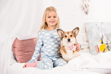 smiling child sitting on bed with pembroke welsh corgi dog with bow at home