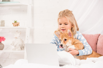 cute child lying in bed with corgi dog and using laptop at home