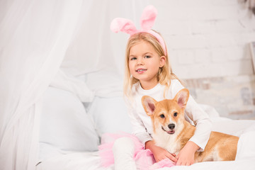 smiling child in bunny ears headband sitting with welsh corgi dog on bed at home