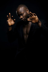 Dark key portrait of young man in black jacket only. Man doing hand dance moves.