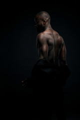 Dark key portrait of sexy man with muscular back, topless, with jacket on arms and chainlet on neck, look from back. Studio shot, black background