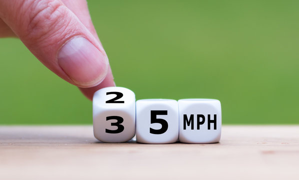 "Hand is turning a dice and changes the expression ""35 MPH"" to ""25 MPH"" as symbol to reduce the speed limit from 35 to 25 miles per hour"