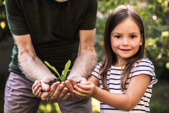 Girl with grandfather holding new plant grown