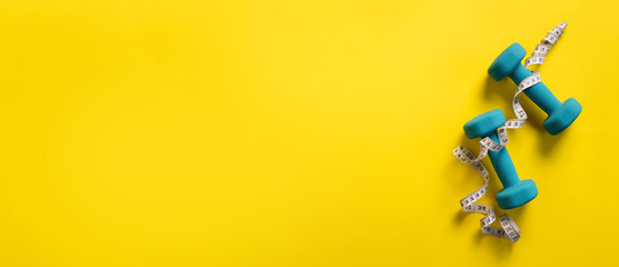 Fitness, sport concept with dumbbells and measuring tape over yellow background. Banner, copy space. Top view. Flat lay