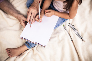 Faceless image of adult man and child with sketchbook sitting on white blanket