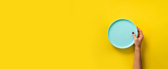Female hand holding empty blue plate on yellow background with copy space. Healthy eating, dieting concept. Banner