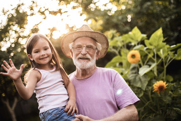 Elderly man with his granddaughter standing between flowers