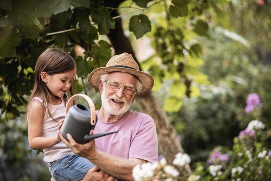 Little girl helping her grandpa watering plants