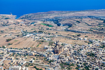 The rotunda of Xewkija (Casal Xeuchia) is the largest in Gozo and its dome dominates the island everywhere. Mgarr ix-Xini bay in background. Rural Gozo island as seen from above. Aerial view of Malta.