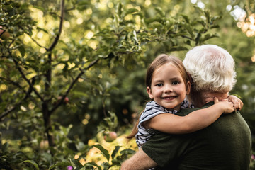 Pretty little girl with her grandfather in garden