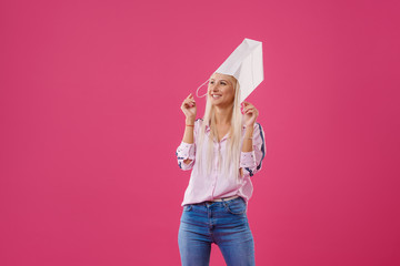Portrait of an excited and fun blond girl with shopping bags on head over pink background