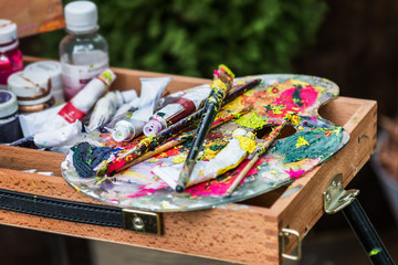 the artist's palette with paints and brushes on the easel