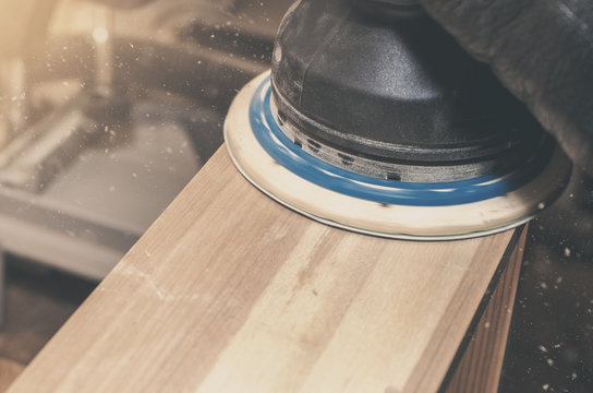 Manual electric grinding machine with emery wheel grinds wooden box, board. Joinery, workshop. Making a wooden products