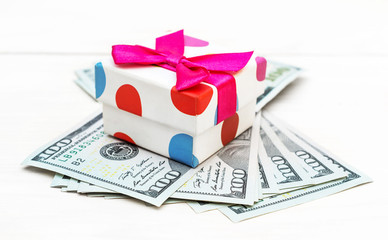 Gift box with dollar bills on white wooden background.