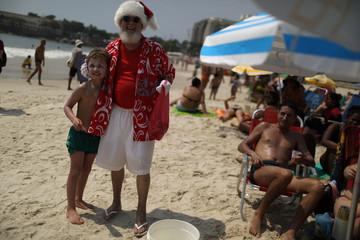Paulo Mourao, who represents Santa Claus poses for a photo with a child at the Copacabana beach in Rio de Janeiro
