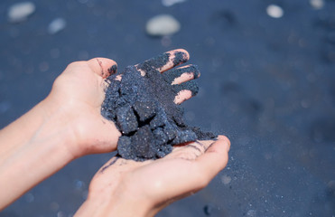 Hands with black volcanic sand